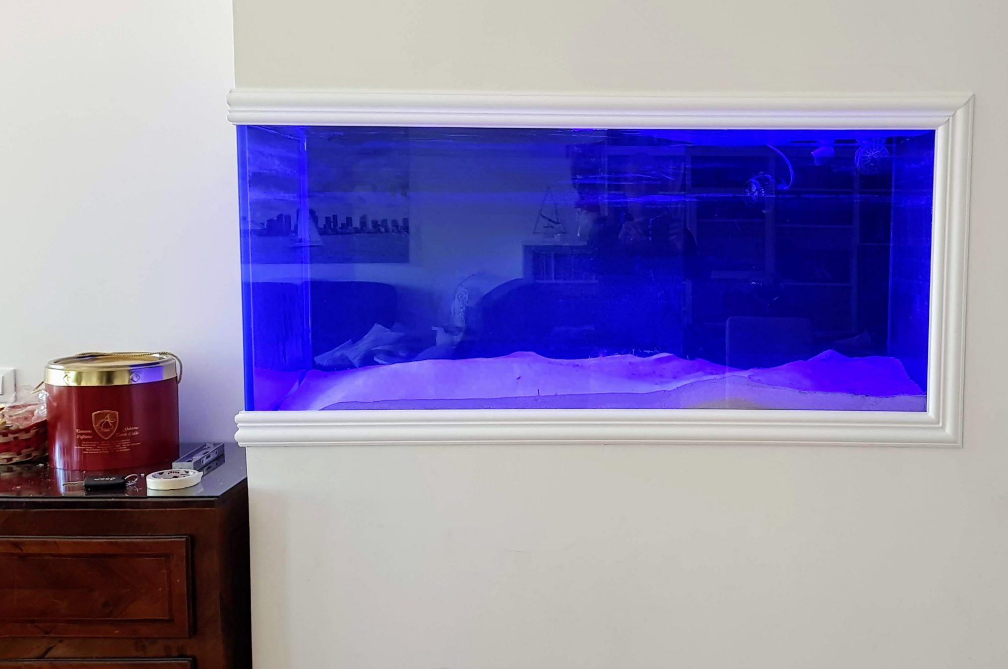 Vista frontale dell'acquario in salotto, appena riempito con la sabbia e decorato con la cornice ai bordi